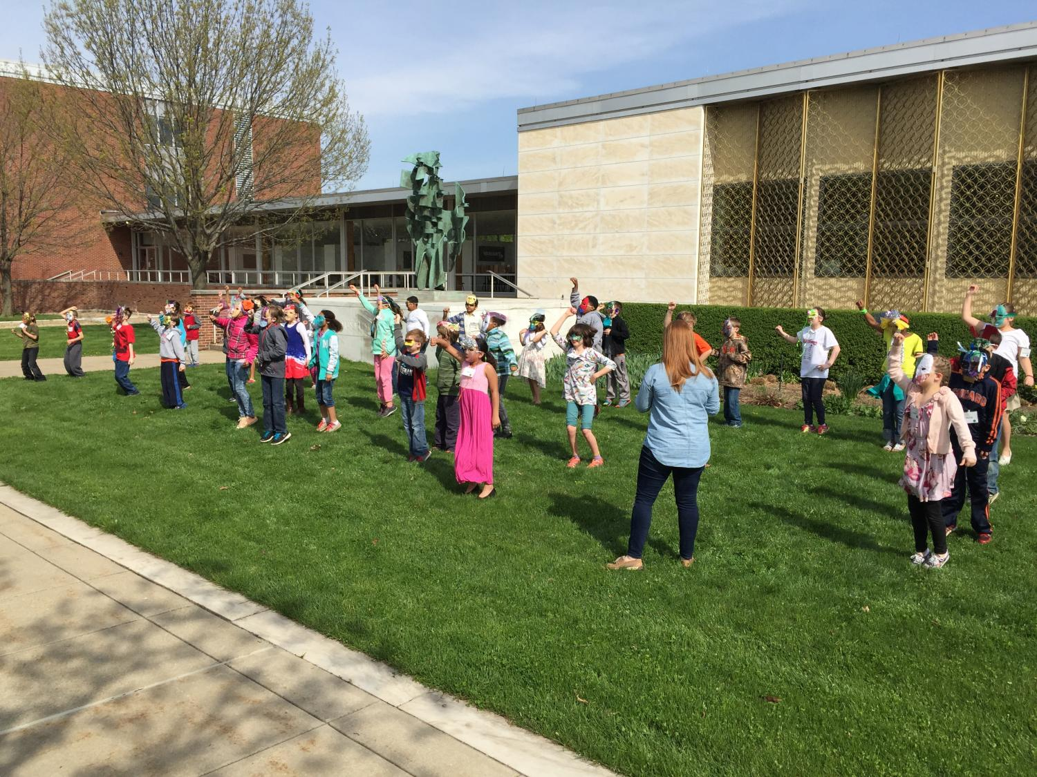 "KAM-WAM students from Robeson and Thomas Paine Elementary schools sing ""Everything Is Awesome!"" from the LEGO' Movie on the lawn in front of Krannert Art Museum"