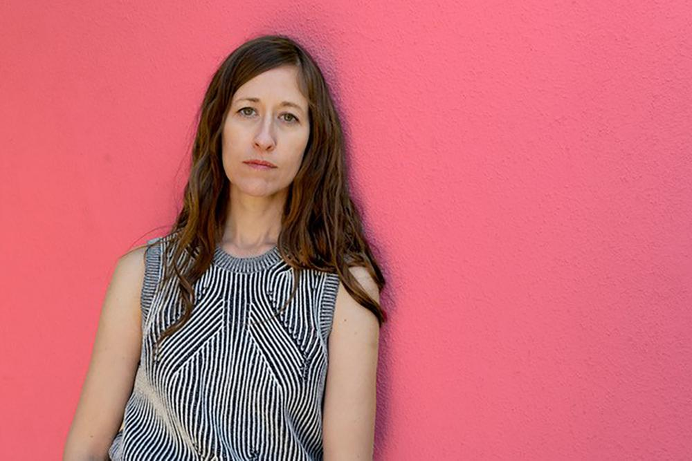 A white woman with long, medium brown hair leans against a rose pink wall. The woman's oval face is neutral, neither smiling or frowning. She wears a sleeveless blouse with a black and white pattern of fine lines, close together.