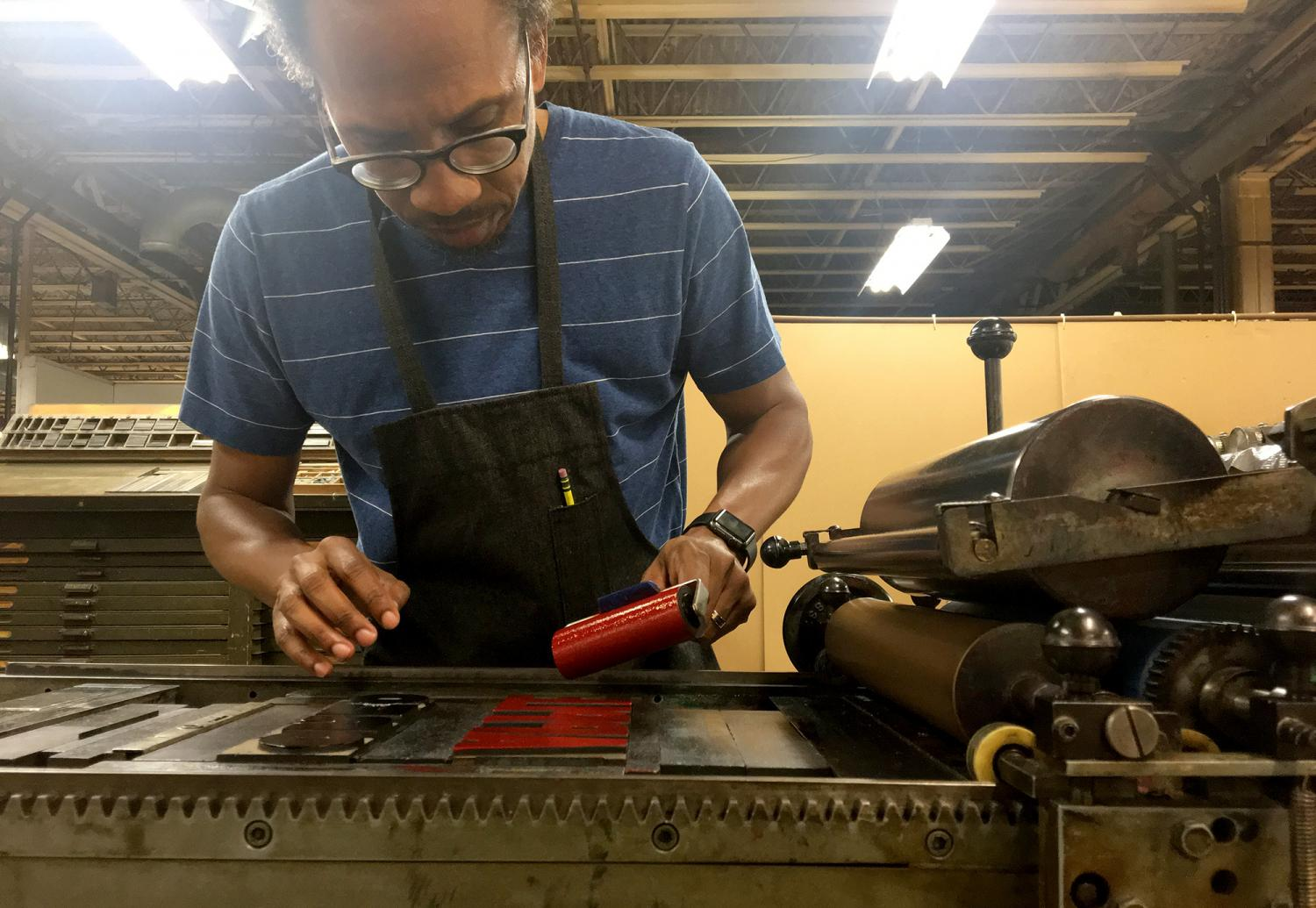 a man, artist Ben Blount, rolling ink onto a letterpress printing machine in a workshop filled with equipment. He is dressed in a printer's apron.