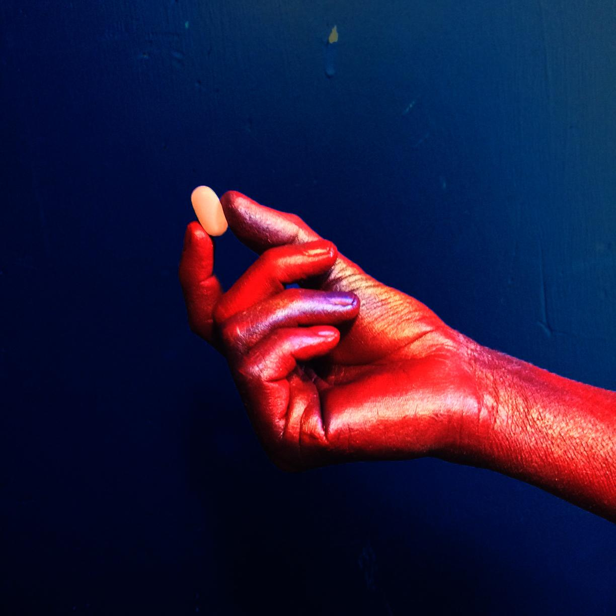 Color photo of a hand holding a pill. The hand is painted red and the background of the photograph is bright blue.