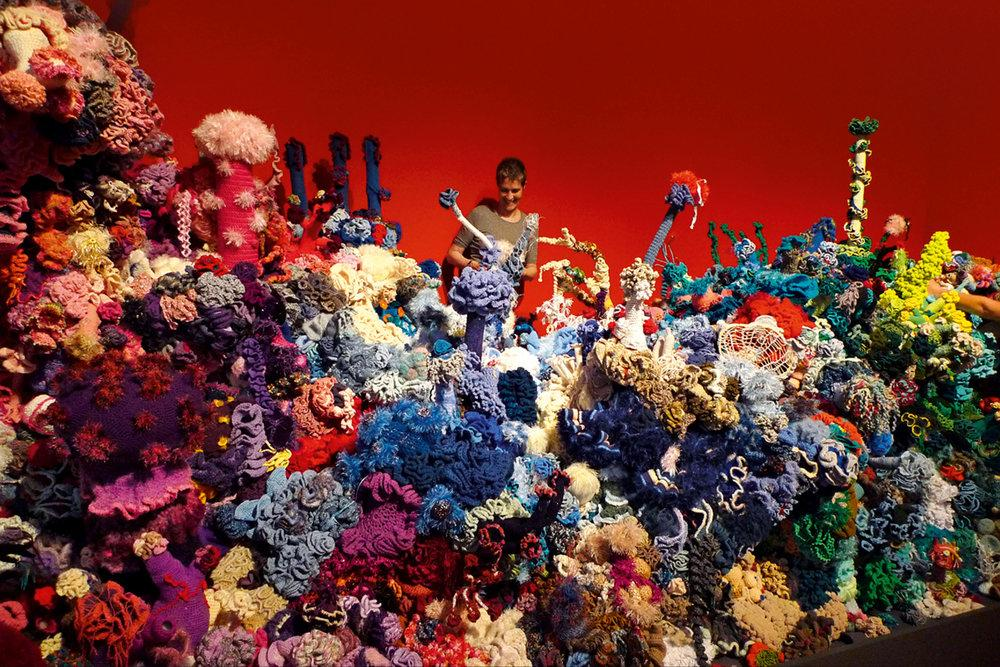 Woman artist standing in the midst of a colorful array of crocheted coral. The arrangement is part of an art installation in Germany, part of the worldwide practice of fiber artist Margaret Wertheim.