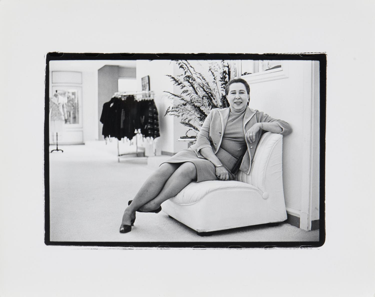 A black and white photograph of a middle aged, heavy-set saleswoman leaning against a divan, smiling. She is in a high end clothing store, spacious and neatly kept. There is a rack of clothing visible in room behind her.