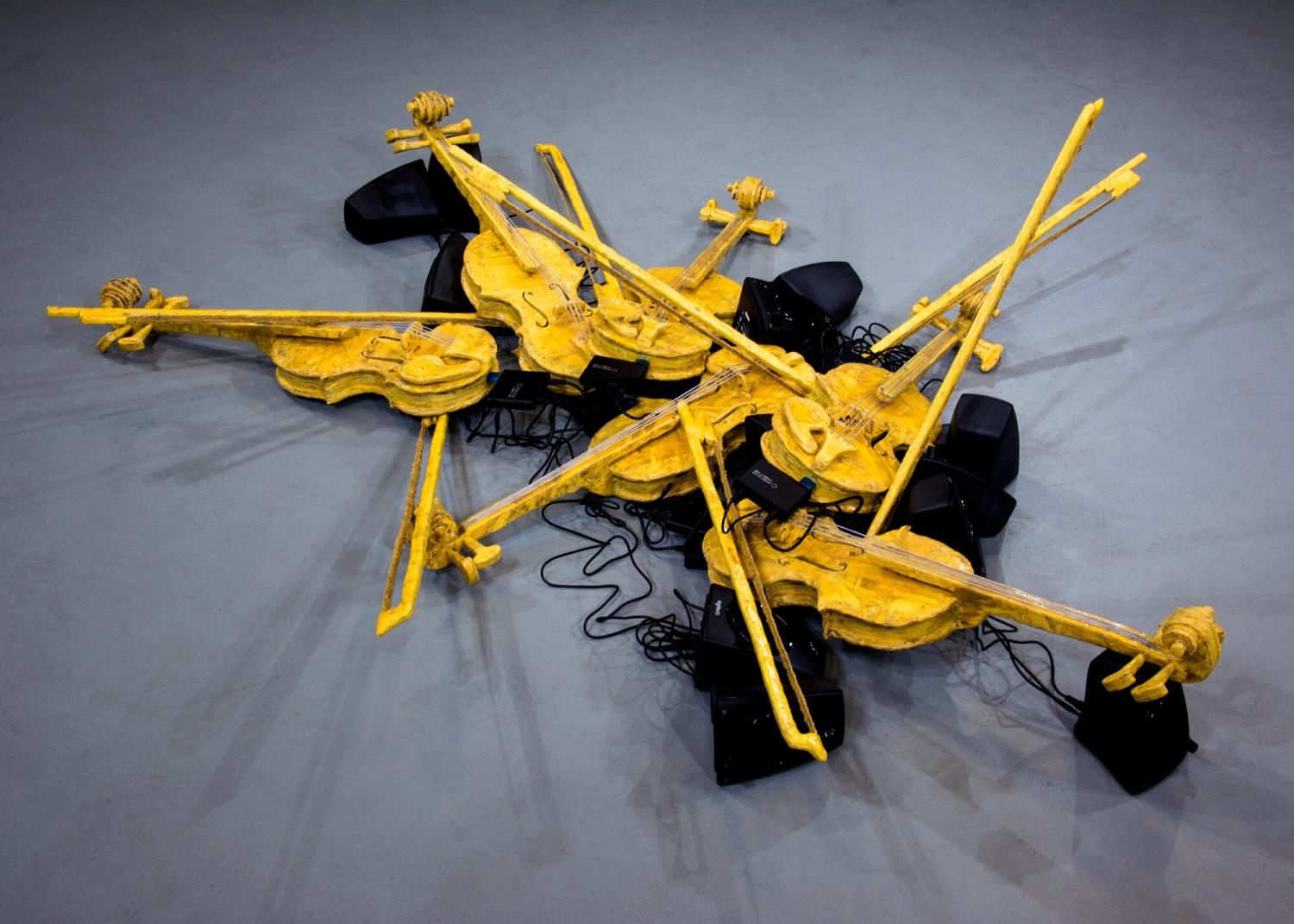 Sculpture made up of assorted yellow and black painted violins and bows, arranged as though they're scattered on the floor. Speakers and wires are intertwined with the sculpture.