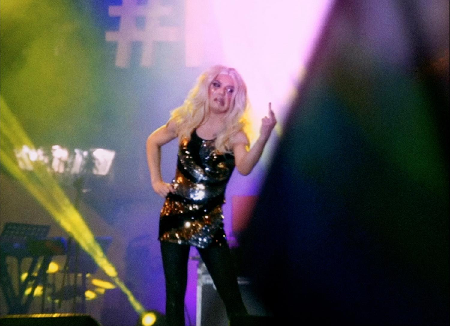 Video still of a drag queen on stage, scowling and giving the audience the middle finger.