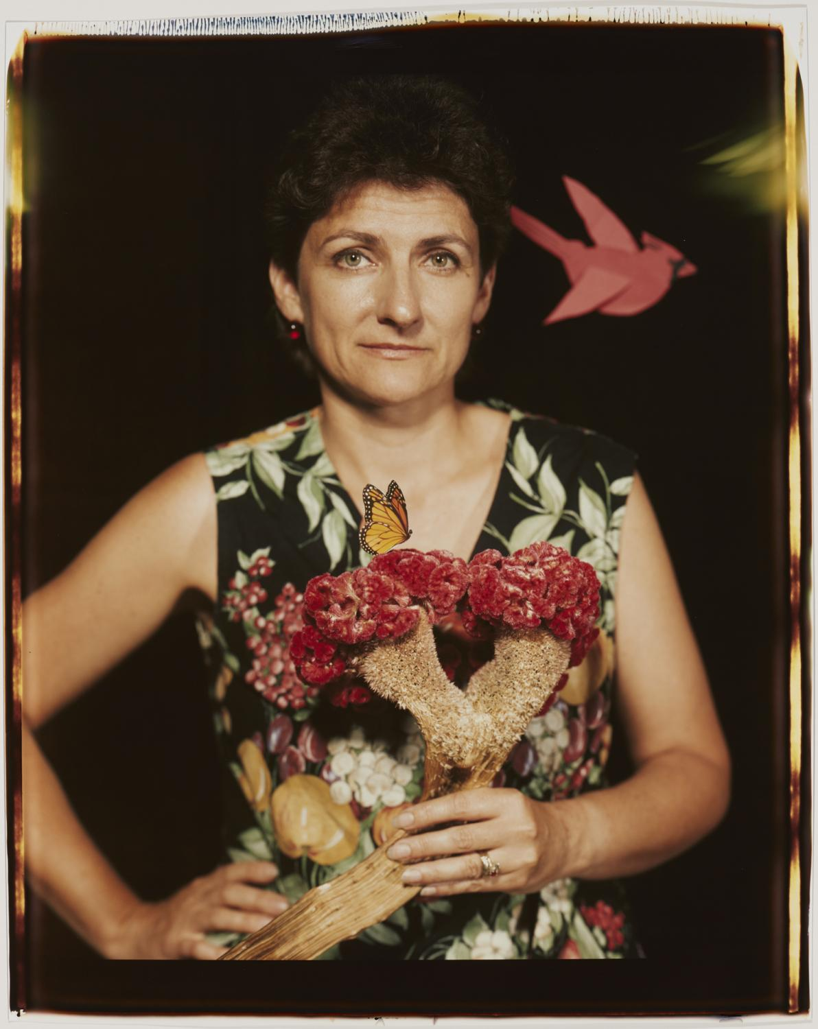 Self-portait of Bea Nettles in a flowered dress standing against a dark background. Her dress is a brightly colored hawaiian print, and she has a flower in her short hair and flowers in her left hand. She smiles slightly at the viewer.