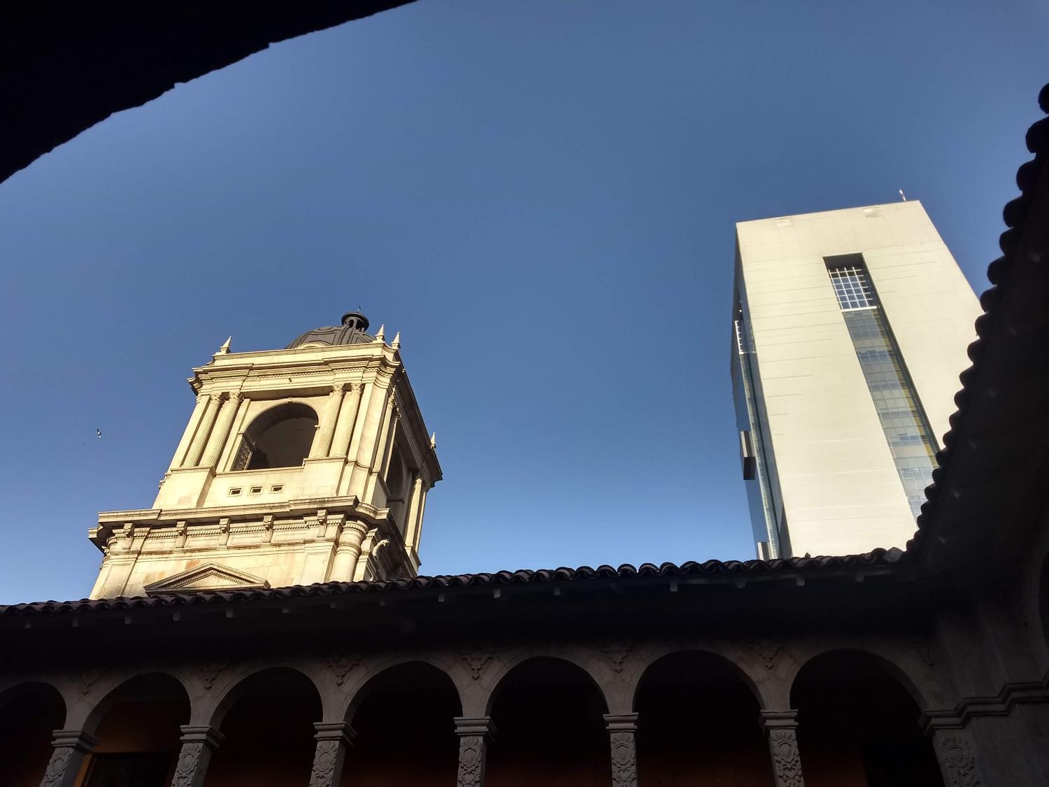 Image of Bolivian skyline with new skyscraper that contains Native imagery in its architecture. The view is looking up from the courtyard of a much more traditional building.