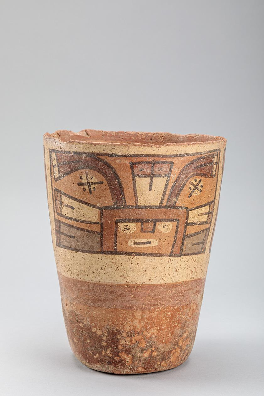 Unglazed pottery cup, reddish brown, with decoration that resembles a mask or masked dancing figure. It is painted in earthtones, like the slip used to paint the figure was made by mixing red or white or black earth into the clay.
