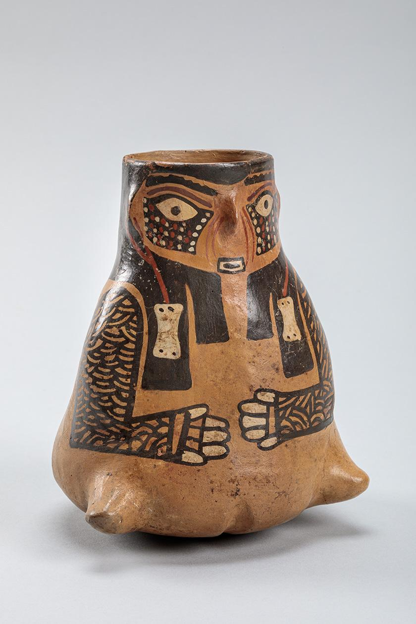 Unglazed open jar resembling a female figure with painted face and clothing. Her hands are drawn to her belly. The decoration is earthtones, as though the slip used for decoration was created by mixing different colors of earth (red, white, black).