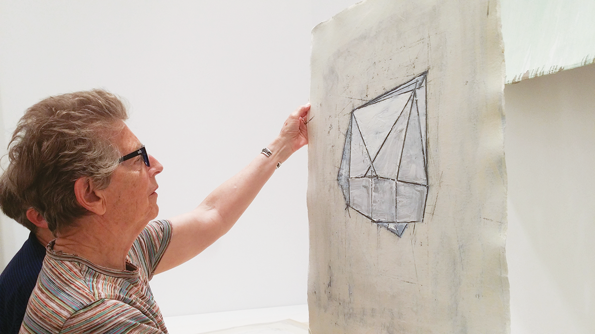Abstract artist Louise Fishman examines her 1976 oil and wax work on paper, My Pigeon (a geometric drawing in white and grey wax on paper), with her spouse Ingrid Nyeboe