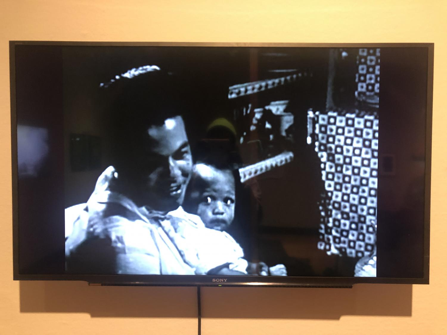 Television with a black and white image of a Black mother smiling. Her baby is seated on her hip, looking up at her. In the background is patterned cloth and a vintage stereo speaker. The snapshot appears to be from the mid to late 20th c. US.
