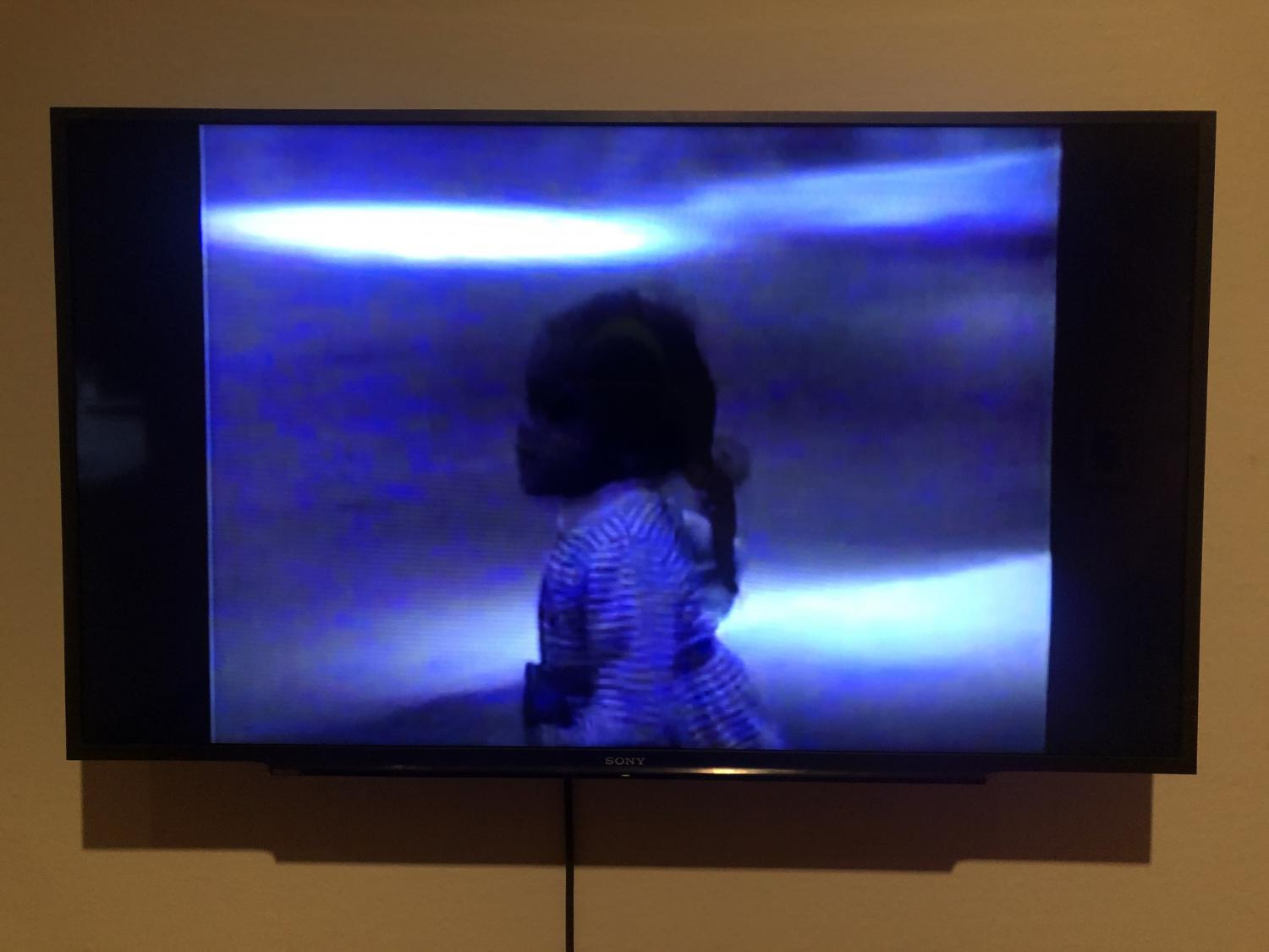 Television with a blue image of an 2-3 year old Black girl with hair braided, turned sideways in profile. She is in a pretty dress.