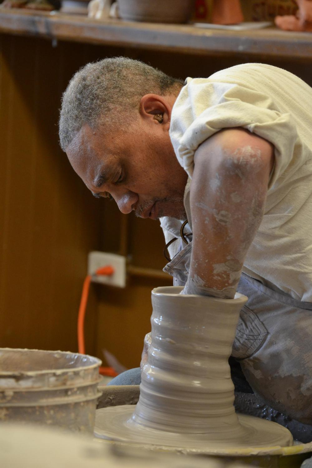 An African American ceramic artist leans forward over his spinning wheel turning a pot. The clay is covered in slip, so appears wet. He concentrates on his work, one hand inside the pot, the other outside, shaping as the clay spins on the wheel.