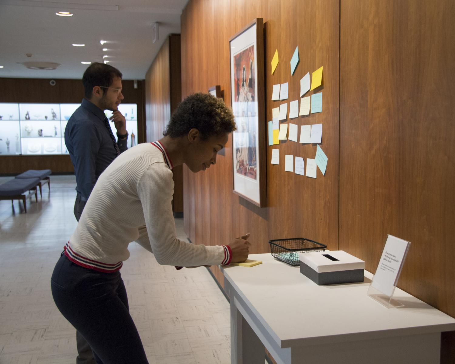 Amber Crawford and Fabian Jimenez engage with KAM's Response Wall, featuring John Clem Clarke's lithograph <em>Louis XIV</em>, 1969.