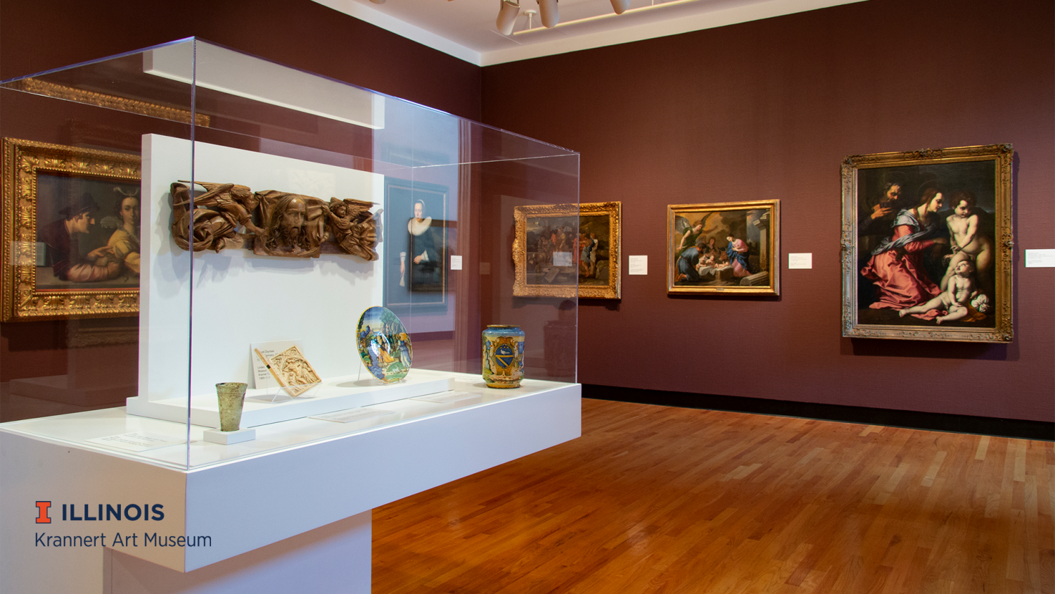 Gallery of European art with a white case with small objects on the left side and a wall with eighteenth and nineteenth century paintings in front of you. The colors in the paintings are rich, with ornate gold frames, and walls are deep burgundy color.