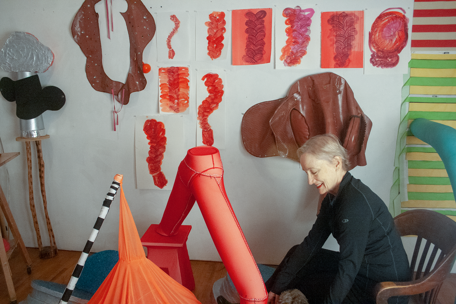 An older woman seated on the right, looking left and down. On the wall are vibrant red-orange drawings of a variety of shapes. In front of the artist are sculptures in similar shapes and red tones with smooth surfaces. The artist looks down and smiles.