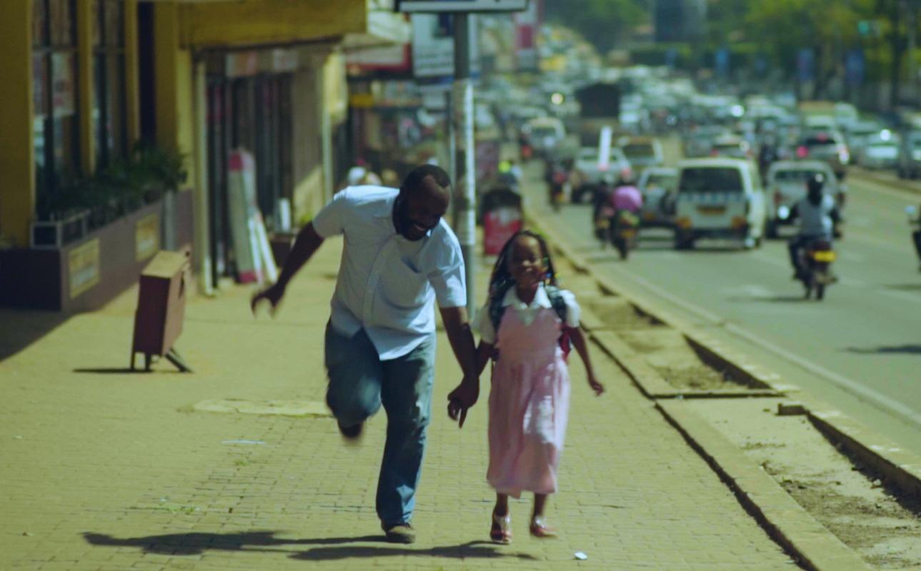 Image of an African man and a young girl (possibly his daughter) running down the sidewalk holding hands and laughing. They are in a city.