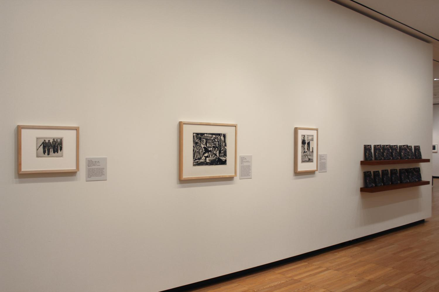 Gallery view of three black and white prints hung on a wall. To the right of the image are several shelves with Pressing Issues brochures on them. The shelves are made of wood and the brochures stand up for visitors to take.