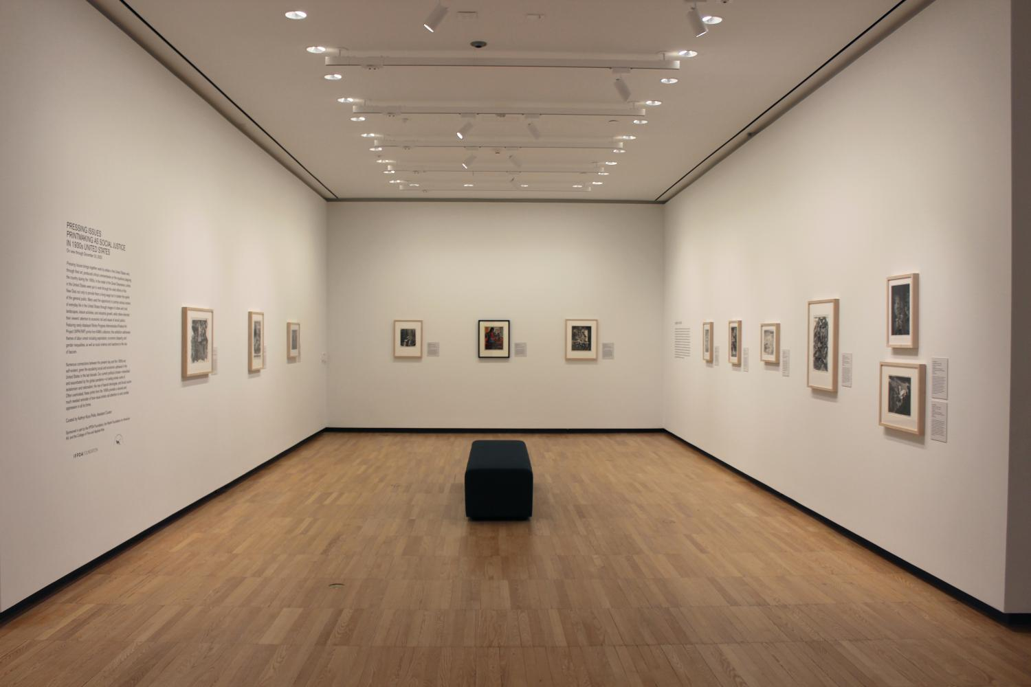 Gallery view of a three-sided space with seating in the middle. The walls are a clean white with framed prints hung on each wall. To the left is title text and the curator's essay for Pressing Issues.
