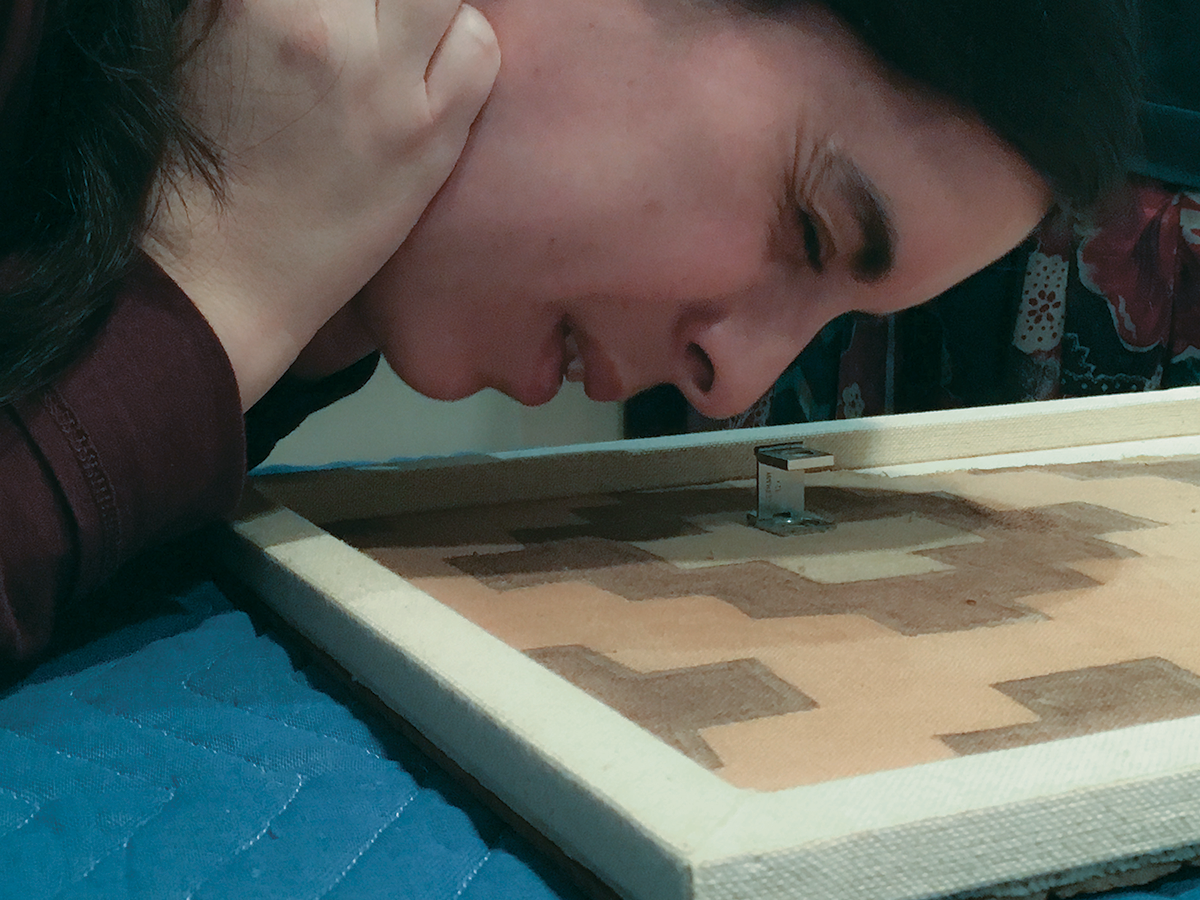 Image of a dark-haired woman leaning close to examine a textile that lays flat on a table. The woman is Andean researcher Rosa Varillas Palacios