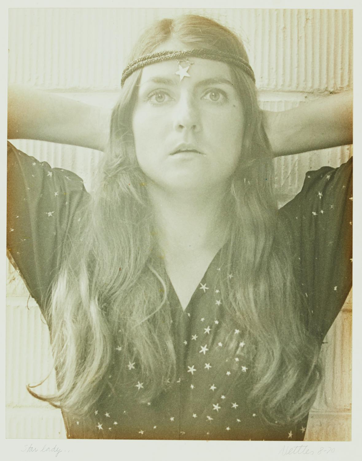 Sepia colored photo of a woman looking wide-eyed at the camera. She has on a star crown over her long, flowing hair and a blouse covered in stars. She is the photographer, and this is a self portrait.