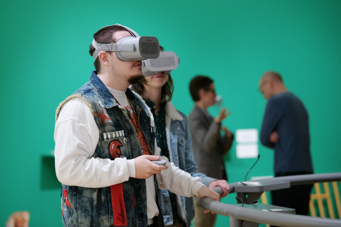 "Visitors watch a 360-degree video on an Oculus headset in an installation titled ""Real World Harm"" at Krannert Art Museum, 2018. Photo by Della Perrone."