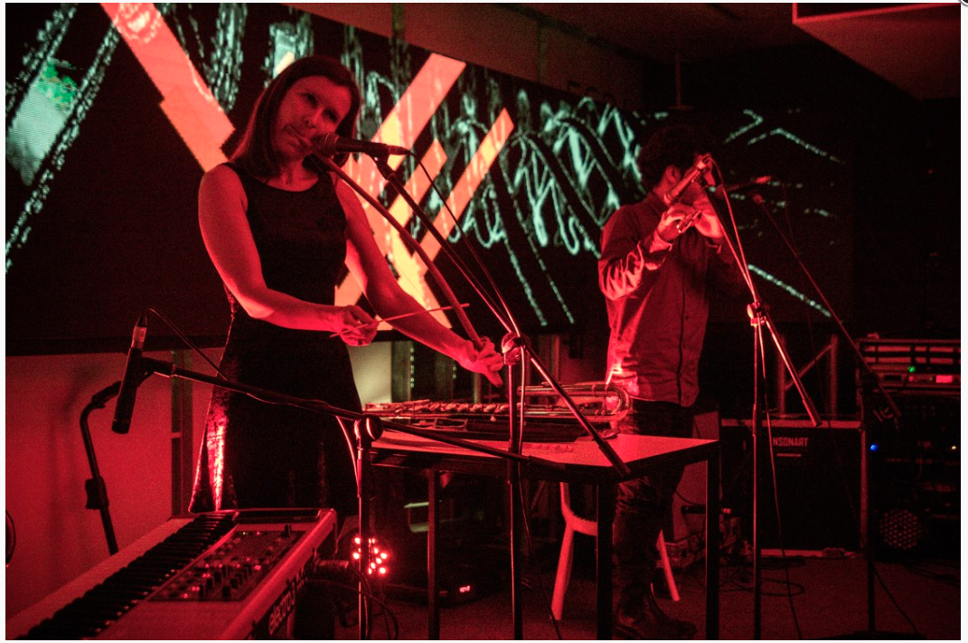 Cara Stacey at left, playing an instrument on stage, surrounded with red light.