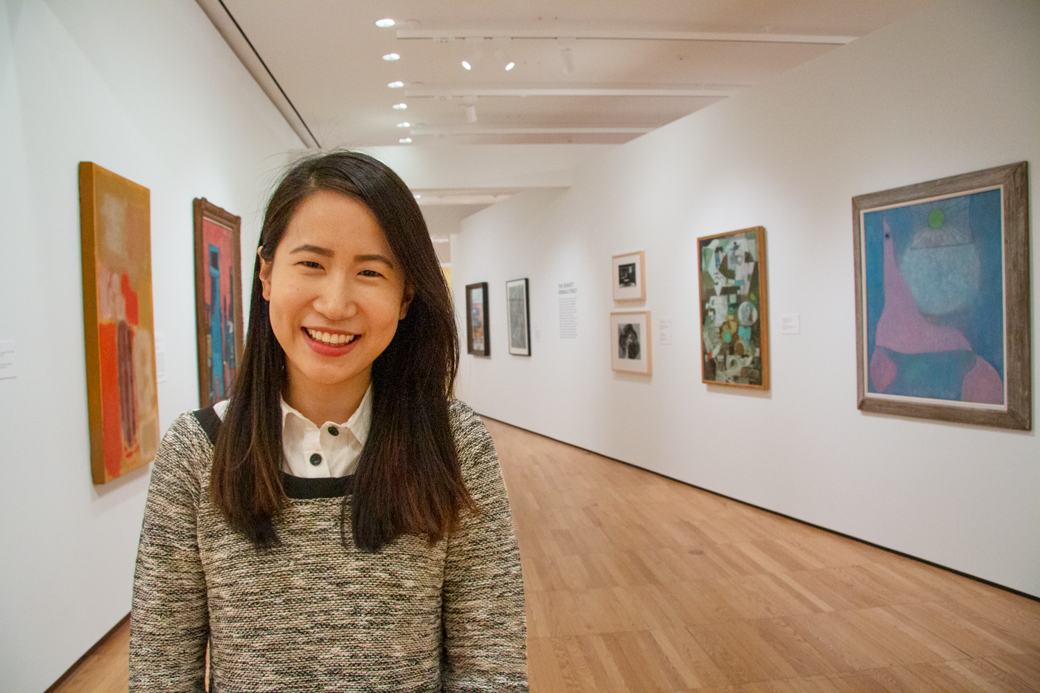 Woman in the foreground with long, black hair, a black/white speckled sweater with a collared shirt underneath. She is smiling and has Asian feature and skin tone. She stands in a hallway with eight modern paintings and photographs on the walls.