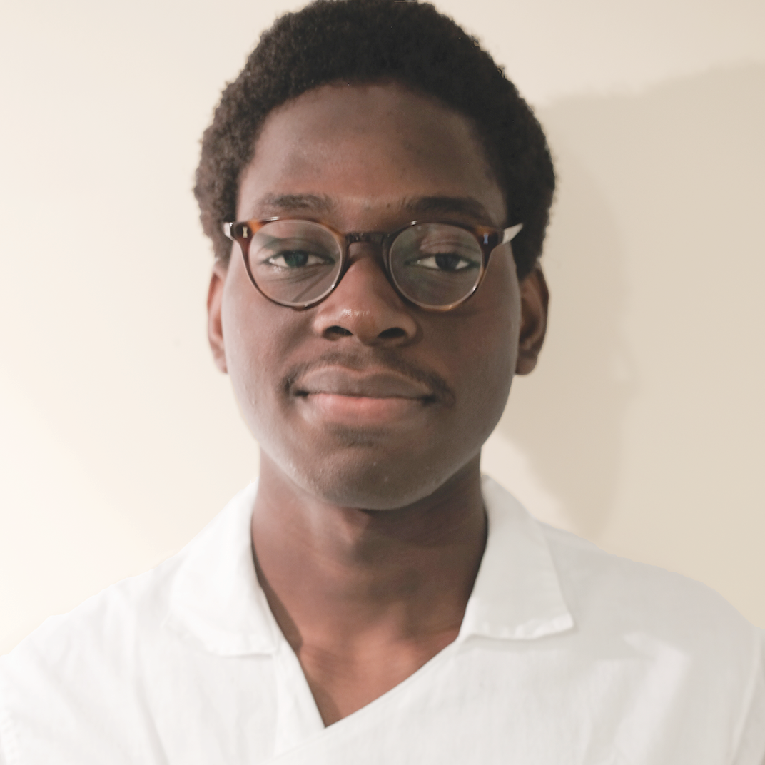 Photo of the face of a young African man in a white collared shirt.