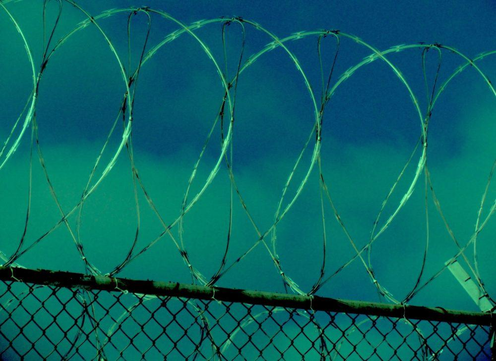 razor wire curls across a green/blue background in a video still from Kathering Cheairs' documentary on women's prisons and the AIDS epidemic