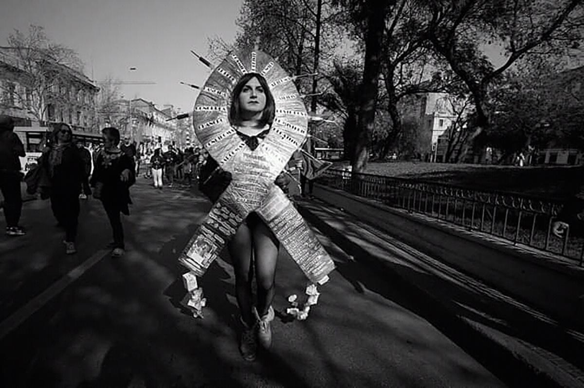 Black and white image of a woman with a large paper cutout framing her face. It is in the shape of a memorial ribbon and is covered with words. She is walking in a parade.