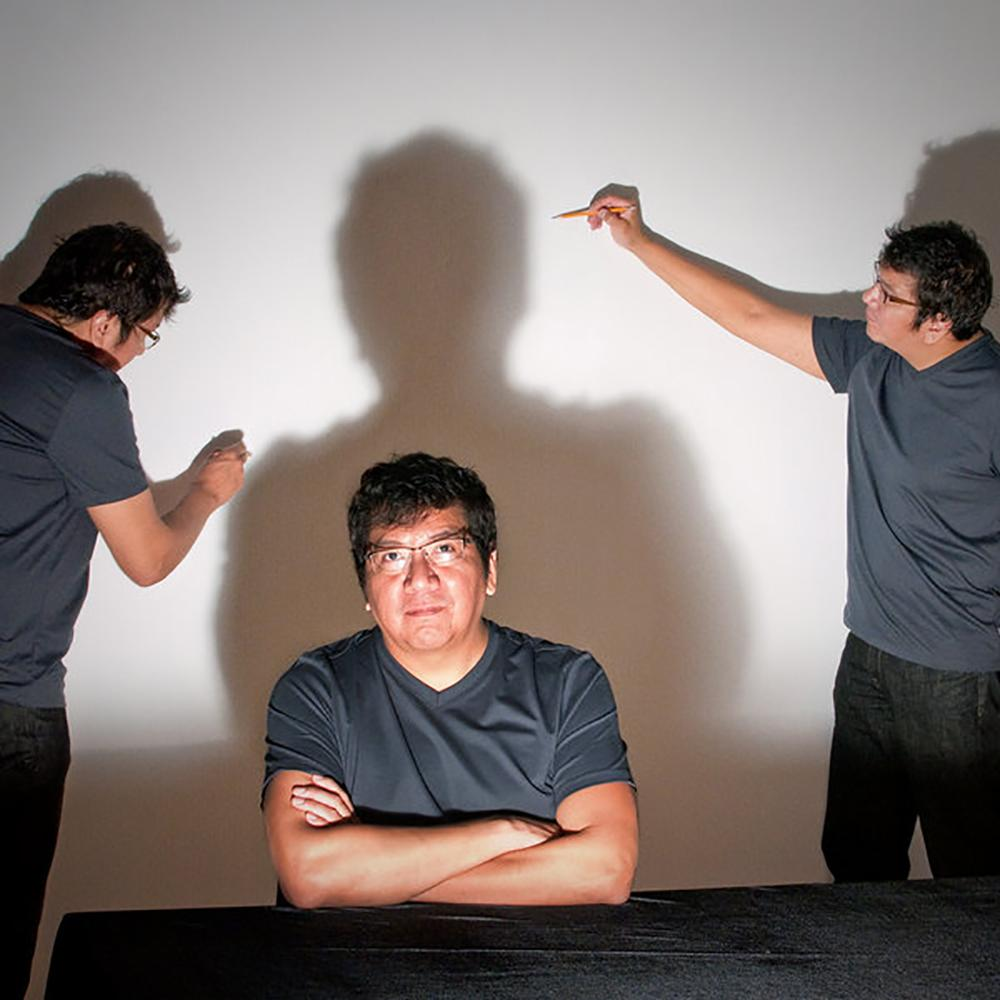 Photo of the artist seated at a table. He has dark hair and glasses and is wearing a t-shirt with his arms crossed. A harsh light shines on him, casting a shadow on the wall. Two other images of the artist stand near the shadow, tracing it with pencil.