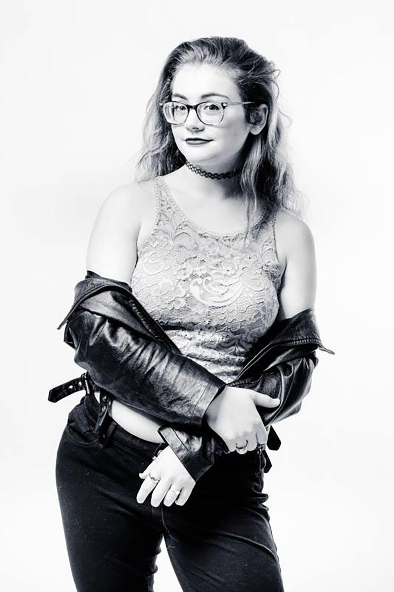 Black and white image of a woman in her 20s with light hair and skin. She has a lace shirt and a leather jacket.