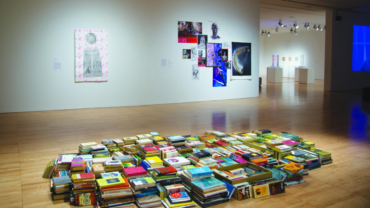 Image of an art gallery installation that contains a pile of paperback book replicas painted by Conrad Bakker and a printed imprint of a nightgown by Gwen Montgomery hangs on the opposite wall. More faculty art can be seen through a doorway.