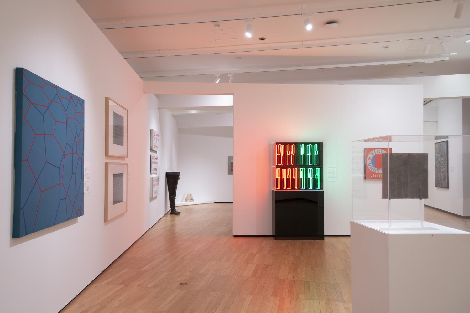 "Art gallery with white walls; at close left is a hard-edge hexagon painting by June Harwood, at center against wall is a pair of hip waders with a dish of water in them 'Body Fluid' by Annette Lemieux, at center right is a neon sign ""Automat"" by Chrissa"