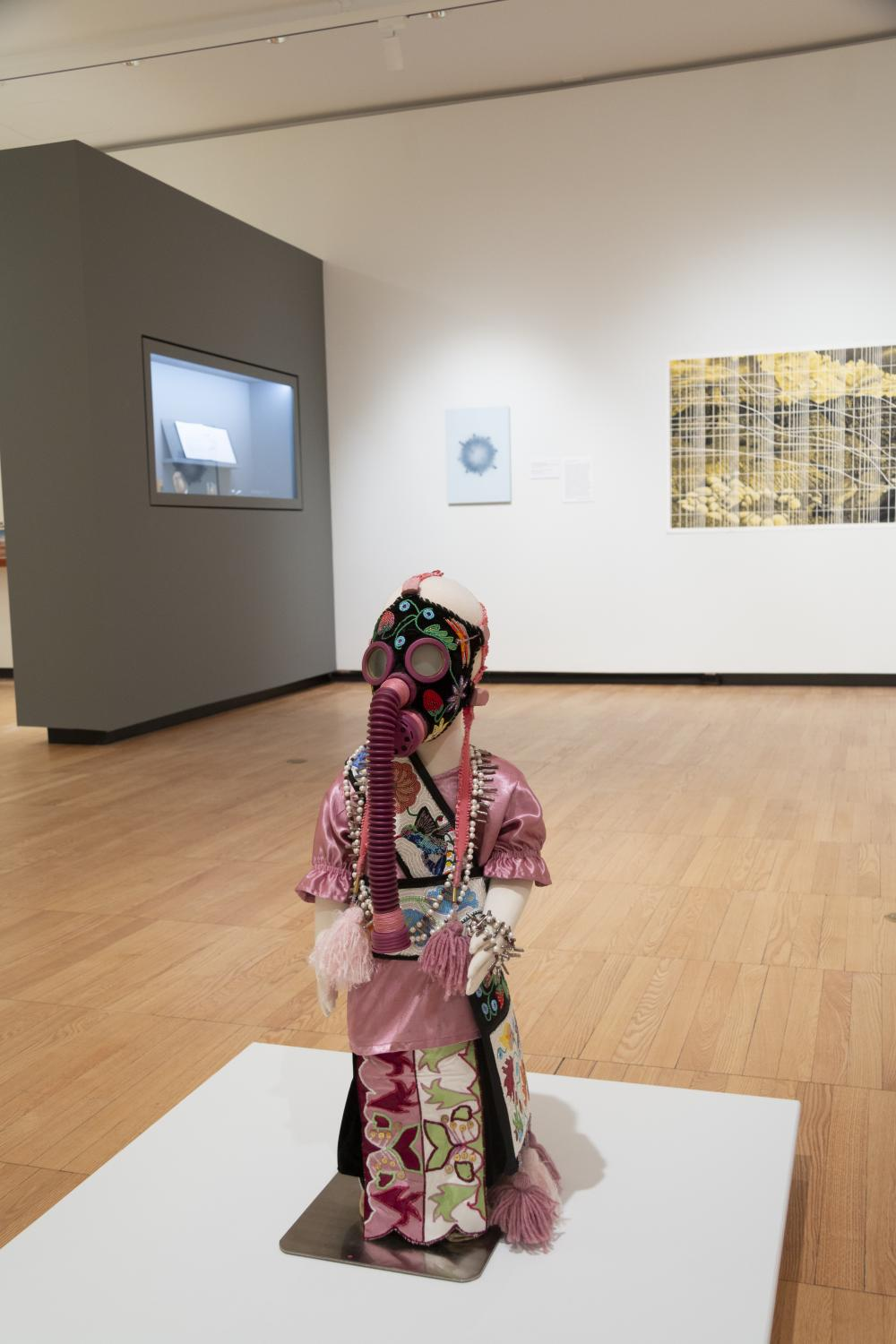 Image of a small mannequin dressed in a beaded satin dress with ornately decorated gas mask, created by artist Naomi Bebo. In background is a grey wall with small objects and a yellow image of a graph overlaying an image of Bears Ears national monument.