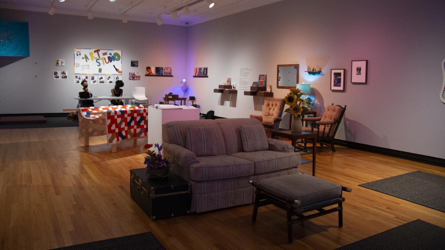 "Image of a gallery with home furnishings, colored lights, and a painted ""Art Studio"" sign. Two Black women sit a table beneath the sign to welcome young people to the gallery for studio art days."
