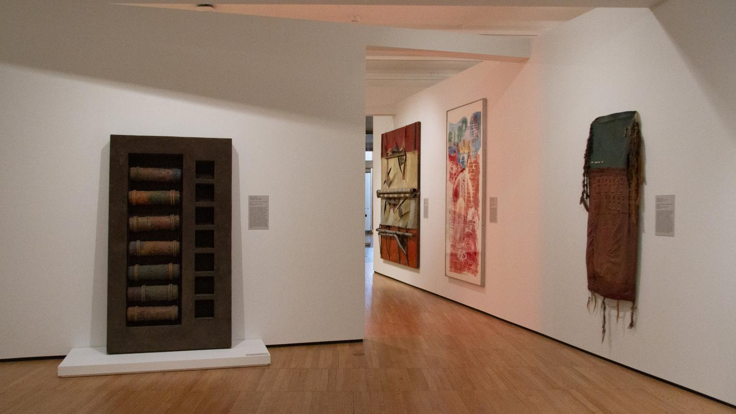 A gallery filled with art, including a large rectangular sculpture leaning against a wall. It has textured rollers to the left and empty box-like shelves to the right. On the right-hand wall are a print and two assemblage works of art.