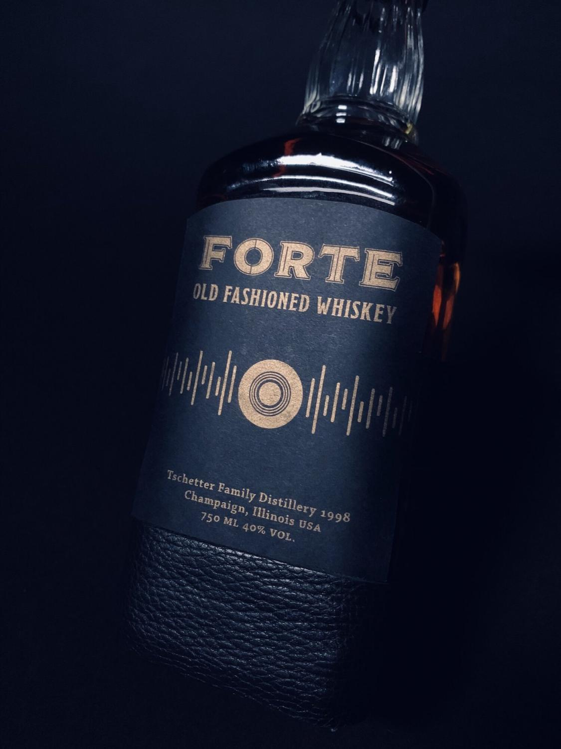 Black whiskey bottle with gold  text that says Forte Whiskey and graphics that look like the bars of an amplifier display. It is a branding concept design by Pascale Grant.