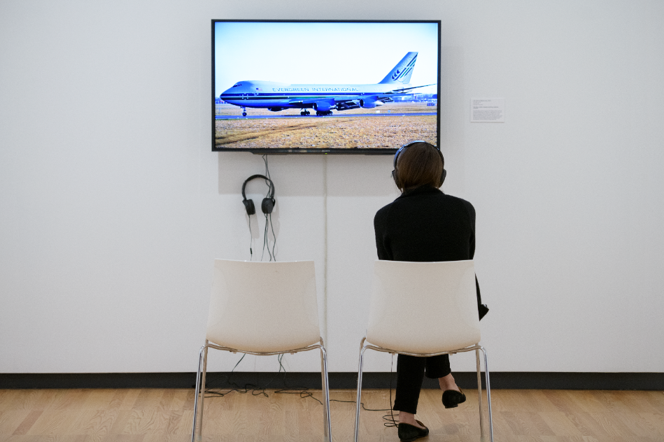 Photo of a young man seated with headphones. His back is turned to the camera because he is watching a video of an airplane on a flat screen tv in an art gallery with white walls.