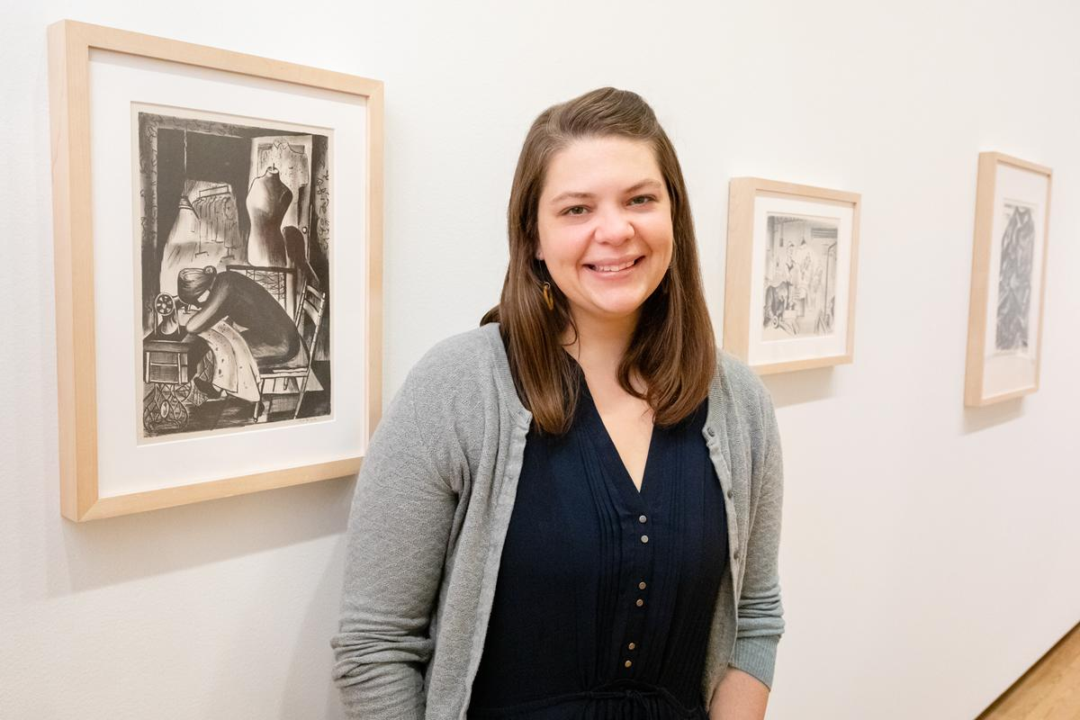 Color photo of a smiling white woman in a grey dress and blue cardigan. She stands in a gallery with WPA prints installed at Krannert Art Museum.