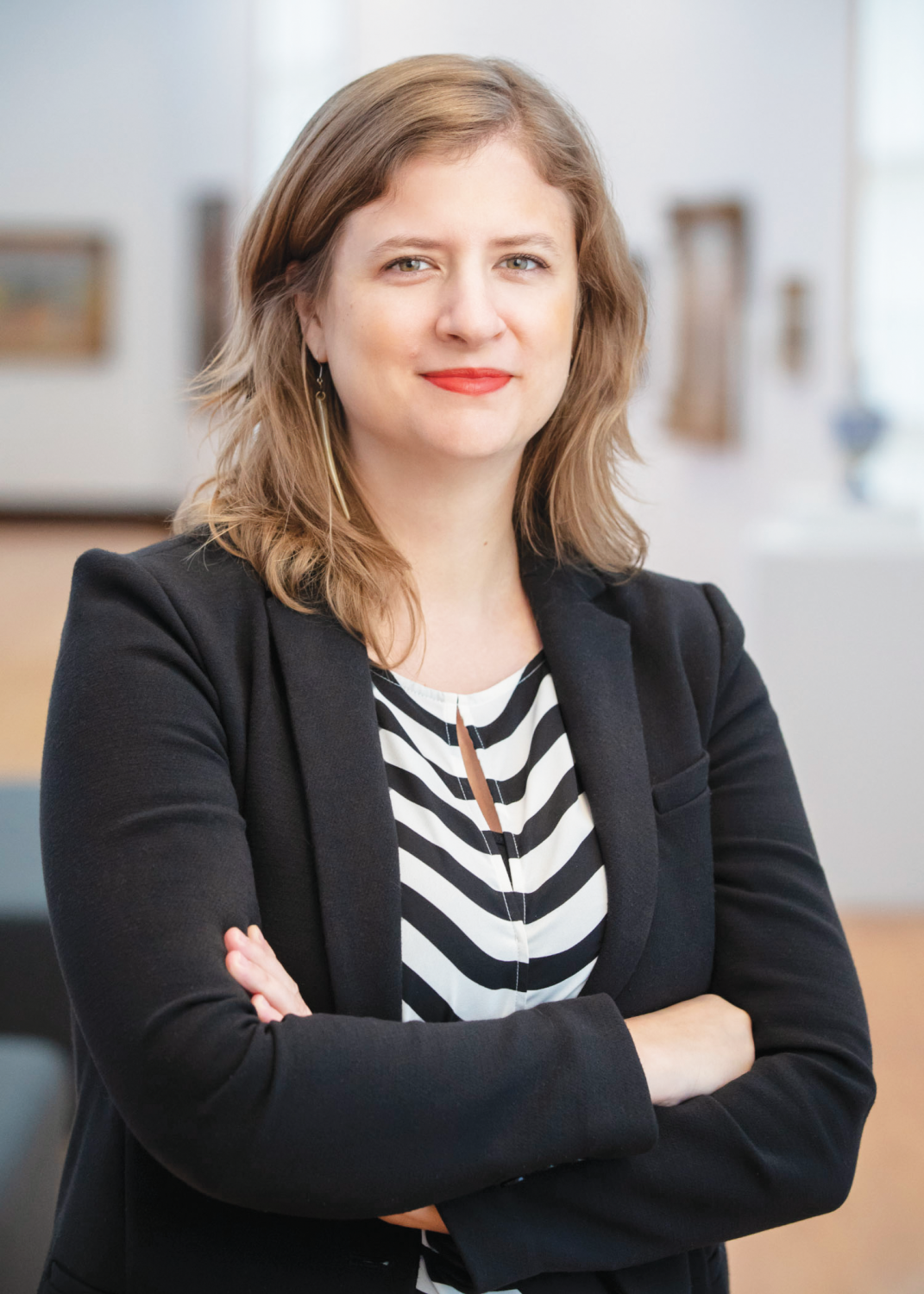 Color photo of Amy L. Powell, Curator of Modern and Contemporary Art at Krannert Art Museum, a white woman with dark blonde hair. She stands in a gallery, professionally dressed with arms crossed in front of her.