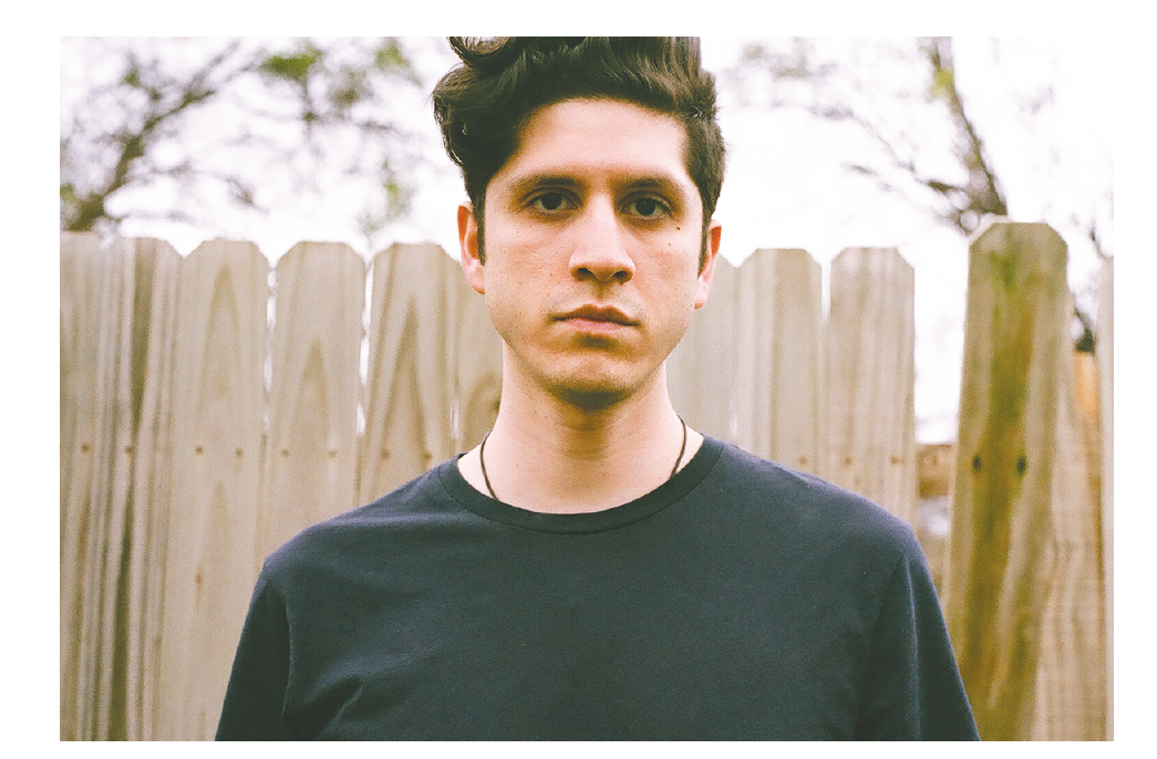 young man with dark, wavy hair and dark eyes gazes at the camera with a serious look. He is standing outdoors with a fence behind him and wearing a dark t-shirt. He is composer Andrew Rodriguez.