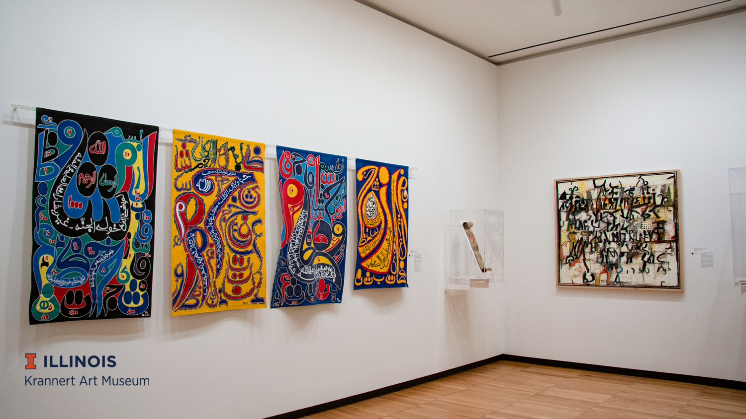 Gallery view of Encounters the Arts of Africa at KAM, featuring fabric panels with arabic script in bright colors by Yelimane Fall (right) and an earth-toned painting by Wosene Worke Kosrof.(left)