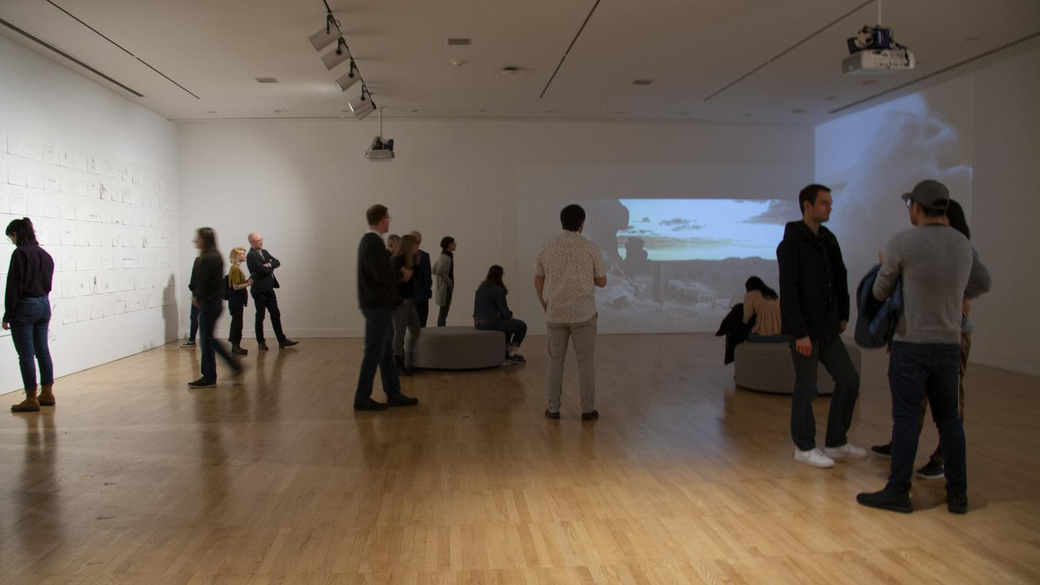 People in a white-walled art gallery viewing an installation of drawings on paper installed on the left wall and two works of video art on the front and right walls.