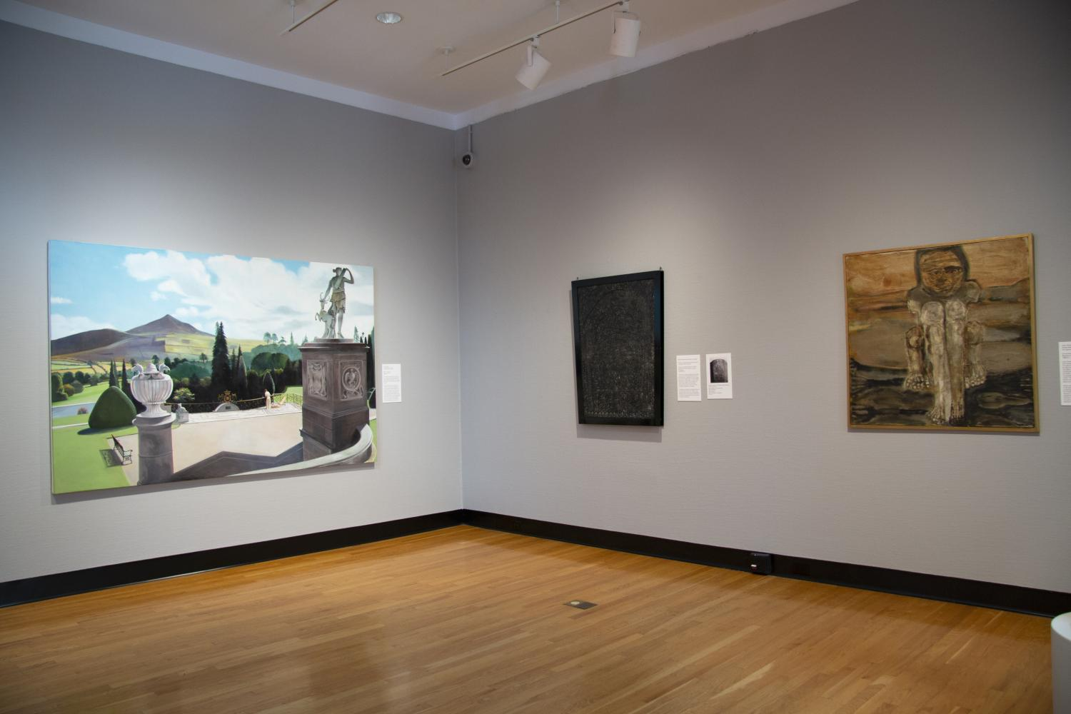 Three paintings on a grey gallery wall. At left is an image of the backs of two pedestals with sculpture and the back of a woman drinking tea looking out over a grand vista. At right are a rubbing of a grave marker and an earth-toned painting of a golem.