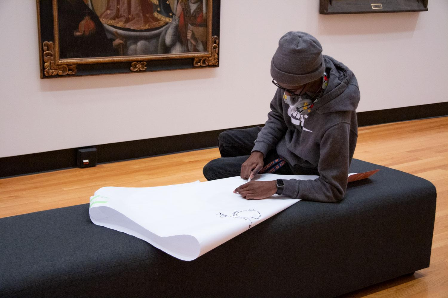 A museum visitor in a grey hoodie and hat semi-reclines on a museum bench to draw on their paper cape. Behind the visitor, who is African American, is a painting of Our Lady of the Remedies of La Paz.