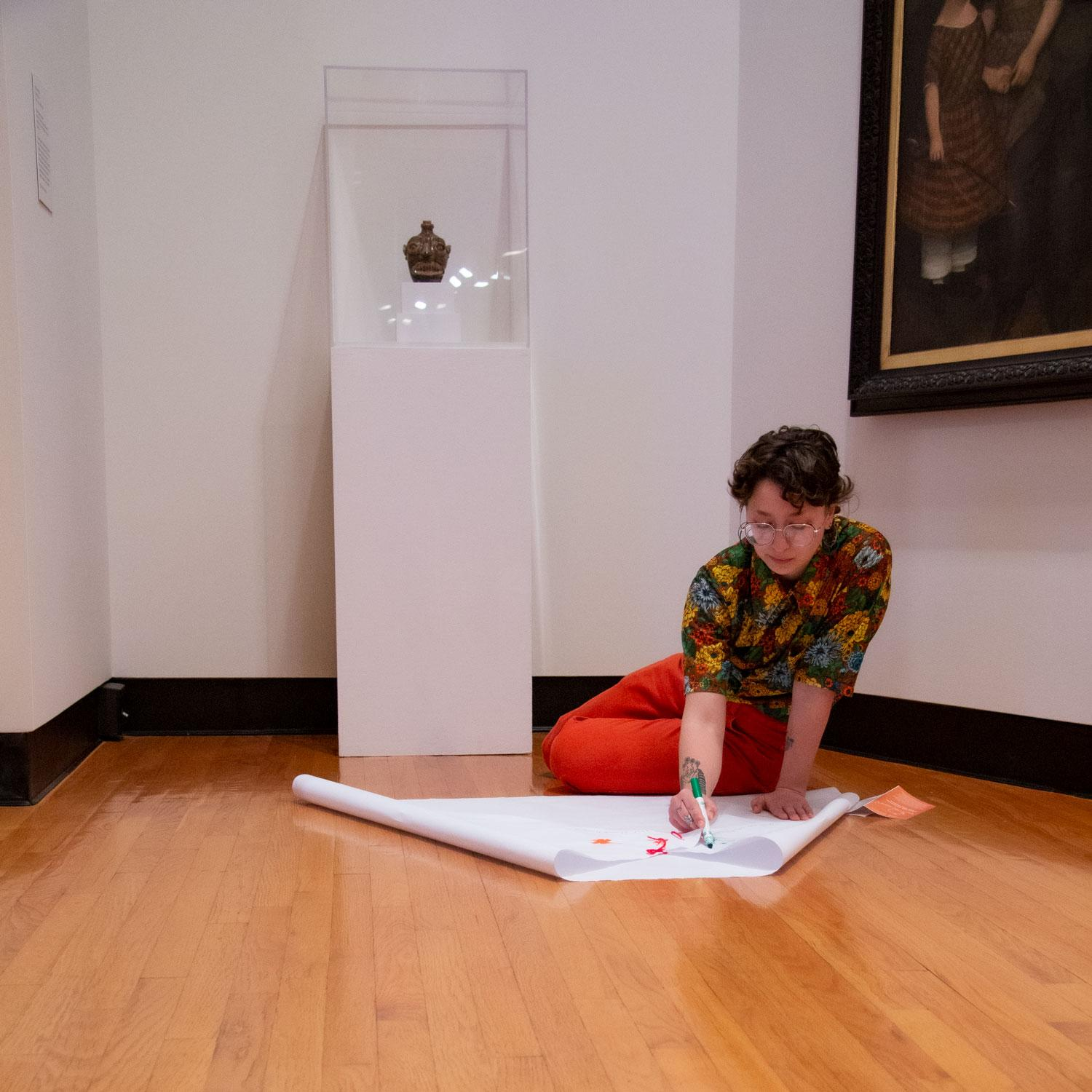 A young woman with short hair, a flowered shirt, and red pants sits on the floor and draws on her paper cape (also on the floor). Behind her is a small, olive green pre-Civil War Face Jug from Edgefield, South Carolina on a pedestal.