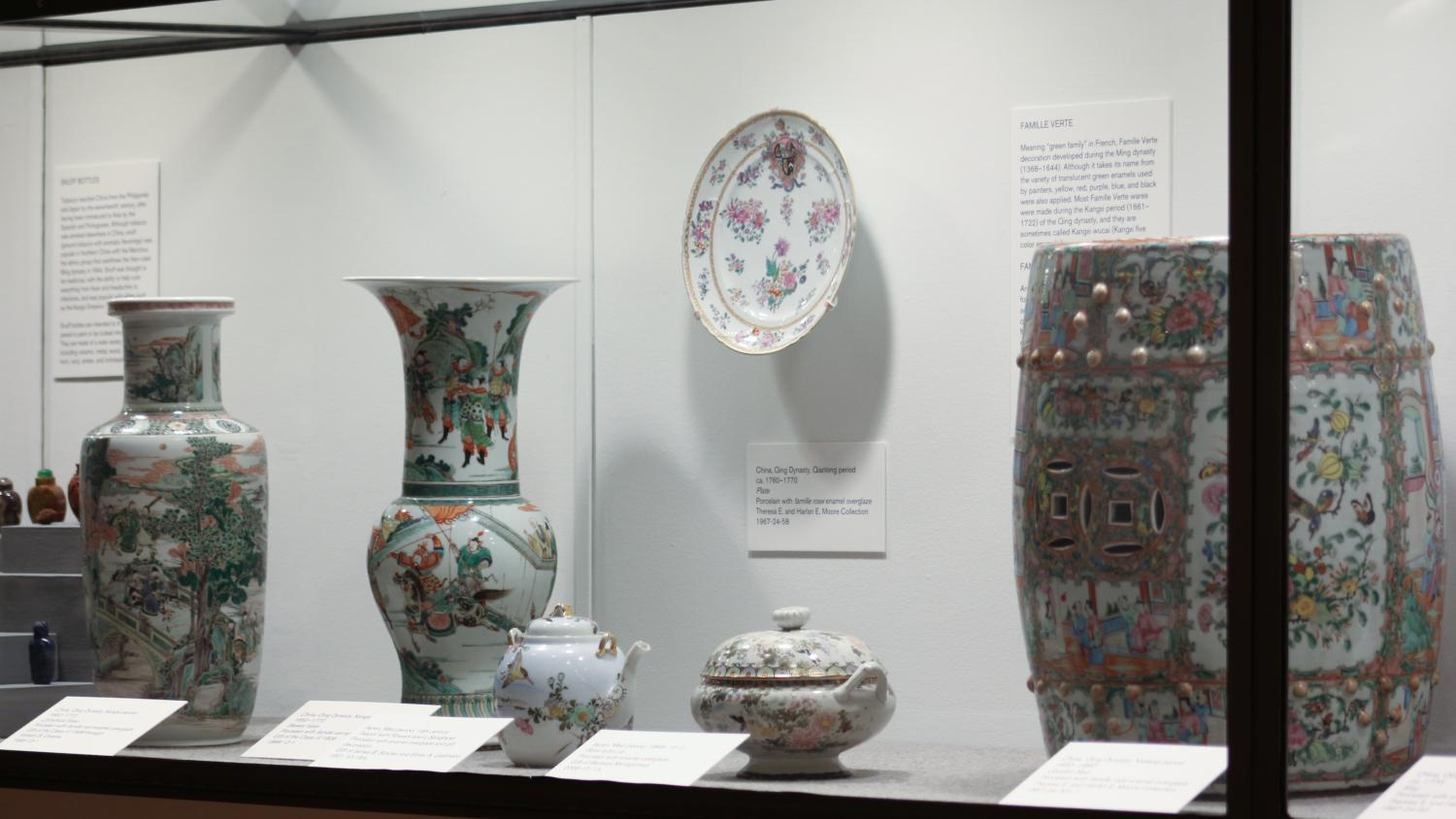 Brightly colored ceramics including a large garden stool with a rose pattern and other smaller pieces with a similar glaze and decorative painting.