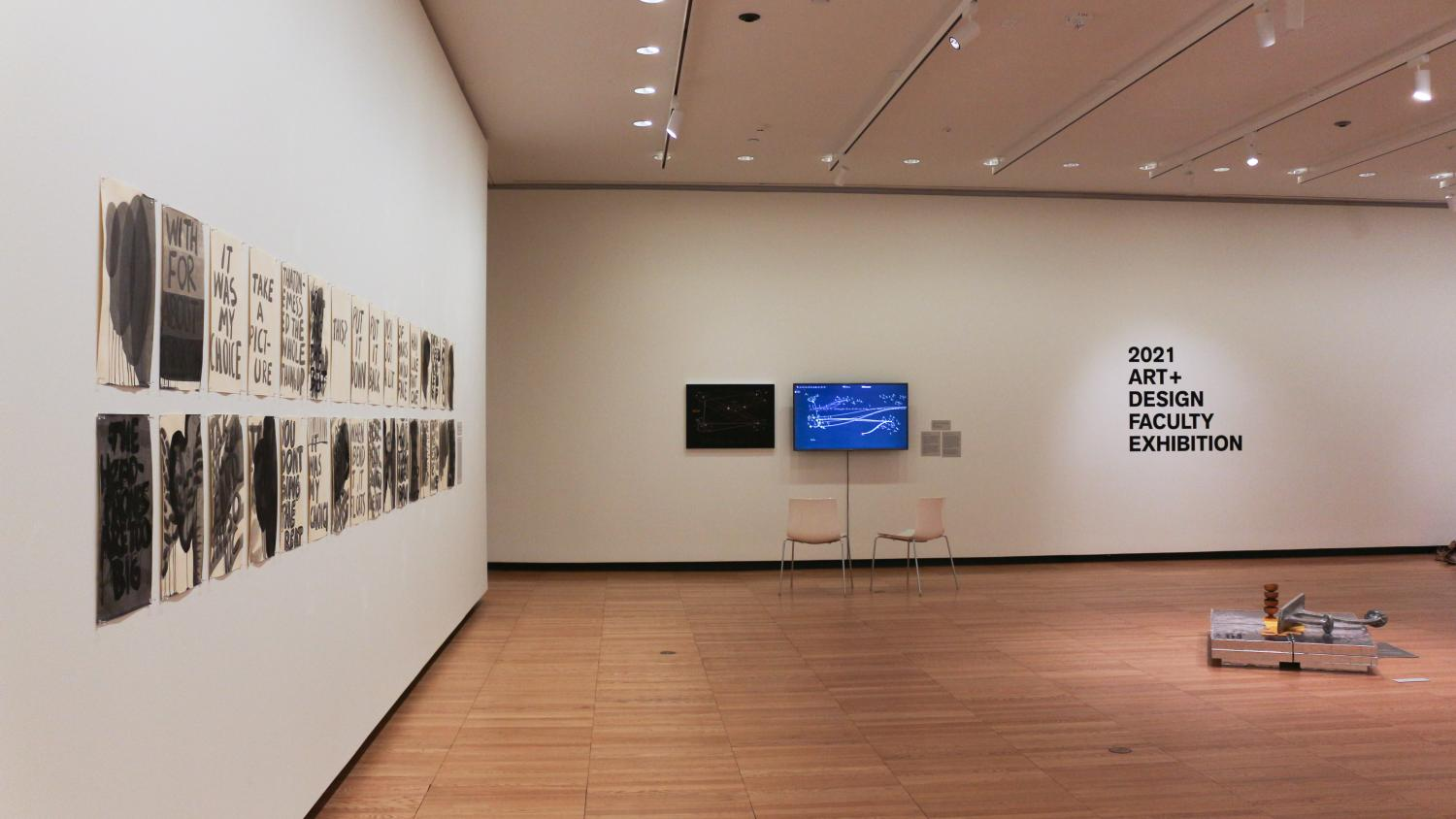 """Installed artwork in Krannert Art Museum's West Gallery, including works on paper, a digital display, and sculpture with the title wall """"2021 Art+Design Faculty Exhibition"""""""