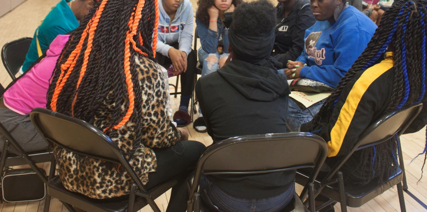 Image of girls talking in a circle during Black Girl Genius Week Champaign 2019 (Urbana Middle School, Urbana, IL), October 2019. Photo by Jen Everett